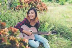 Молодая красивая женщина битника играя гитару сидя на траве внутри Стоковые Фотографии RF