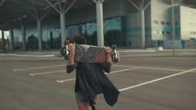 Молодая красивая женщина битника идя на улицу и продолжая скейтборд или longboard рук