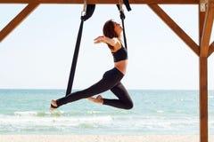 Молодая красивая женщина брюнет делая йогу мухы Сидеть в hammoc Стоковое Изображение