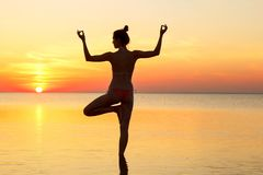Молодая красивая женщина брюнет делая йогу на заходе солнца на пляже Стоковое Изображение RF
