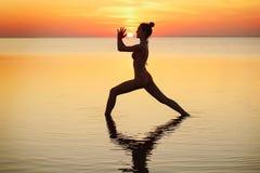 Молодая красивая женщина брюнет делая йогу на заходе солнца на пляже Стоковое Изображение