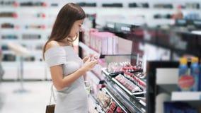 Молодая красивая женщина выбирает губную помаду в косметиках ходит по магазинам, замедленное движение видеоматериал