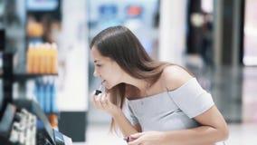 Молодая красивая женщина выбирает губную помаду в косметиках ходит по магазинам, замедленное движение акции видеоматериалы
