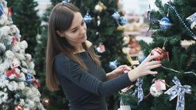 Молодая красивая женщина выбирает украшения для рождественской елки в супермаркете видеоматериал