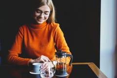 Молодая красивая женщина выпивая от чашки в ультрамодном городском кафе стоковое изображение