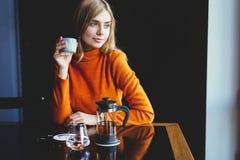 Молодая красивая женщина выпивая от чашки в ультрамодном городском кафе стоковые фото