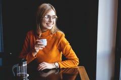 Молодая красивая женщина выпивая от чашки в ультрамодном городском кафе стоковое изображение rf
