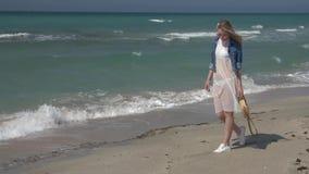 Молодая красивая женщина в белой прозрачной куртке платья и джинсовой ткани идя вдоль seashore видеоматериал