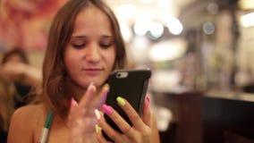 Молодая красивая женщина в вине напитков кафа и мобильном телефоне польз на светах bokeh на предпосылке 1920x1080 видеоматериал