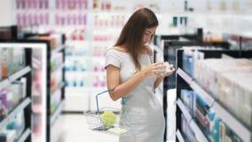 Молодая красивая женщина в косметиках ходит по магазинам выбирает сливк стороны и тела, замедленное движение сток-видео