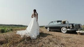 Молодая красивая женщина в платье свадьбы представляя около винтажного автомобиля сток-видео
