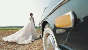 Молодая красивая женщина в платье свадьбы представляя около винтажного автомобиля видеоматериал