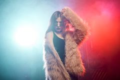 Молодая красивая женщина в розовой меховой шыбе Предпосылка дыма и неонового света Стильные отклоняя танцы девушки на партии Стоковые Изображения RF
