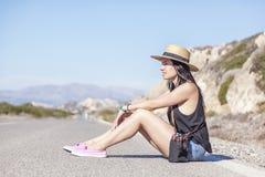 Молодая красивая женщина в шляпе сидя на дороге против b Стоковая Фотография RF