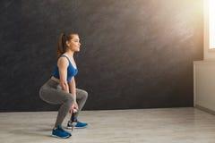 Молодая красивая женщина в sportswear делая сидение на корточках Стоковая Фотография