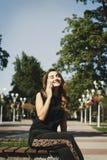 Молодая красивая женщина говоря на телефоне сидя в парке Стоковые Изображения