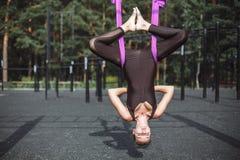 Молодая красивая женщина делая воздушную практику йоги в пурпурном гамаке outdoors стоковые фото