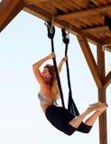 Молодая красивая женщина делая йогу мухы Сидеть в гамаке с na Стоковое Изображение RF