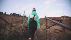 Молодая красивая женщина идя на лестницы водя к пляжу на заходе солнца ( акции видеоматериалы