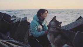 Молодая красивая женщина идя с сибирской сиплой собакой на пляже на заходе солнца, замедленном движении акции видеоматериалы