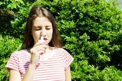 Молодая красивая женщина используя брызг носа в парке стоковая фотография rf