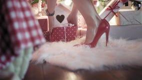 Молодая красивая женщина на высоких красных пятках кладет подарок на рождество под рождественскую елку Закройте вверх по ногам вз акции видеоматериалы