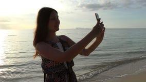 Молодая красивая женщина на пляже делая selfie во время захода солнца или восхода солнца видеоматериал