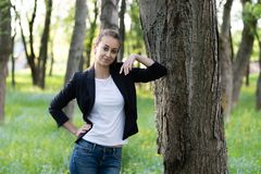 молодая красивая женщина нося куртку дела и белую верхнюю часть стоит с ее локтем на стволе дерева стоковая фотография rf