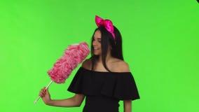 Молодая красивая женщина нося розовый смычок представляя с сыпней акции видеоматериалы