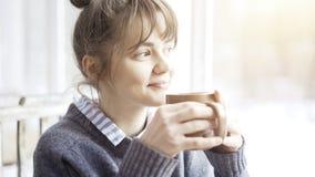 Молодая красивая женщина нося серый свитер наслаждается ее чаем в кафе и daydreaming стоковое изображение