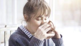 Молодая красивая женщина нося серый свитер наслаждается ее чаем в кафе и daydreaming стоковое изображение rf