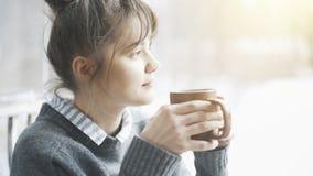 Молодая красивая женщина нося серый свитер наслаждается ее чаем в кафе и daydreaming стоковые фотографии rf