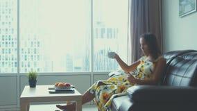 Молодая красивая женщина ослабляет на кожаном диване дома смотря кофе улыбок и напитков фильма 3840x2160 акции видеоматериалы