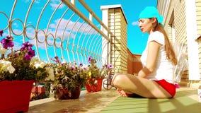 Молодая красивая женщина ослабляя на балконе после фитнеса или йоги Стоковое Изображение RF