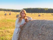 Молодая красивая женщина остается близко стогом сена на летнем дне Стоковое Фото