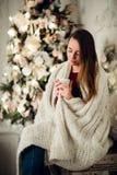 Молодая красивая женщина при сидя дом держа чашку горячего кофе нося связанный теплый свитер рождество моя версия вектора вала по Стоковые Фото