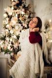 Молодая красивая женщина при сидя дом держа чашку горячего кофе нося связанный теплый свитер рождество моя версия вектора вала по Стоковые Изображения RF