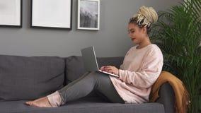 Молодая красивая женщина работая на ноутбуке и усмехаясь на удобной софе дома сток-видео
