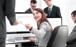 Молодая красивая женщина рассматривает графики сидя на ее рабочем месте стоковое фото