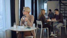 Молодая красивая женщина сидя на таблице и выпивая кофе крытых Стоковое фото RF