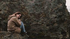 Молодая красивая женщина сидя на утесе в горах и думая самостоятельно Турист отдыхая после пешего туризма в Исландии видеоматериал