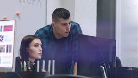 Молодая красивая женщина смотря монитор компьютера и обсуждая что-то с ее сотрудником Человек poining его палец На сток-видео
