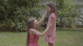 Молодая красивая женщина с длинными волосами сидя на траве и petting ее дочь в саде Время траты семьи акции видеоматериалы