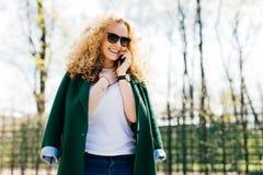 Молодая красивая женщина с курчавыми солнечными очками белокурых волос нося и зеленой курткой говоря на ее мобильном телефоне, ус стоковые фотографии rf