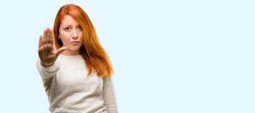 Молодая красивая женщина redhead над голубой предпосылкой стоковое фото rf