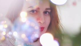 Молодая красивая загадочная женщина смотря камеру через света гирлянды на запачканном bokeh на акции видеоматериалы