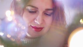 Молодая красивая загадочная усмехаясь женщина смотря через света гирлянды движение медленное 3840x2160 видеоматериал