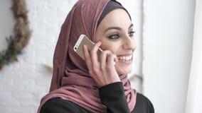 Молодая красивая индийская девушка в hijab смотря прочь, смотрящ камеру, усмехающся, говоря на smartphone, портрет  сток-видео