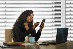 Молодая красивая и занятая черная Афро-американская коммерсантка используя деятельность мобильного телефона на столе с ноутбуком  стоковое фото