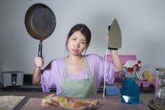 Молодая красивая и разочарованная азиатская корейская женщина держа лоток и утюг усилила и осадка сокрушанная отечественными рабо стоковое изображение